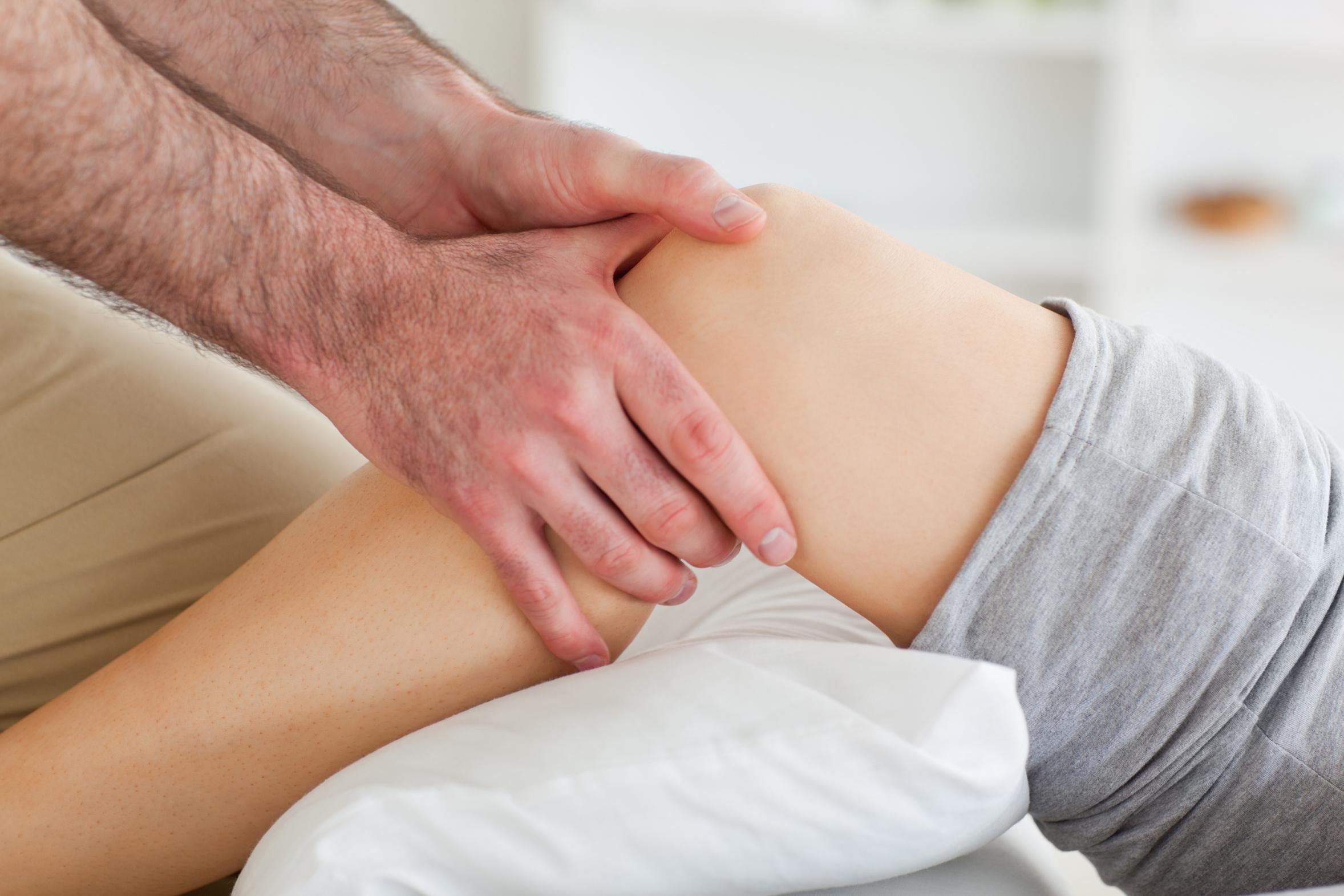 Man massaging a woman's knee